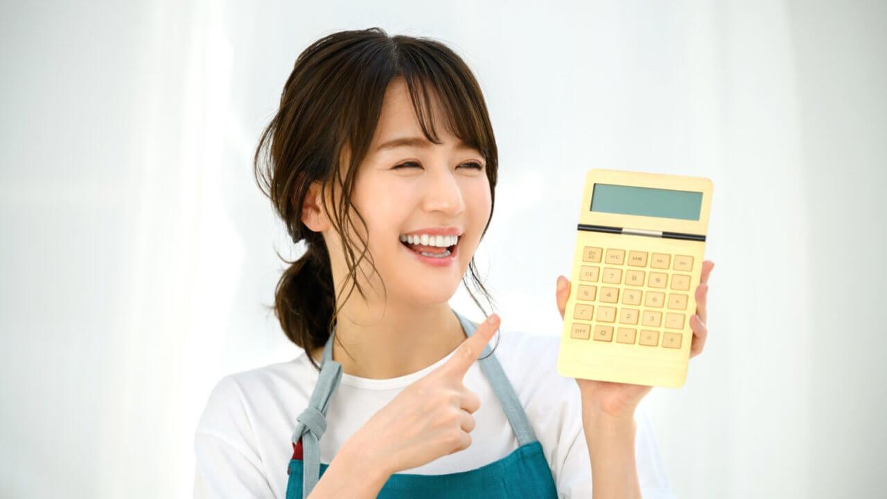 笑顔で電卓を見る女性