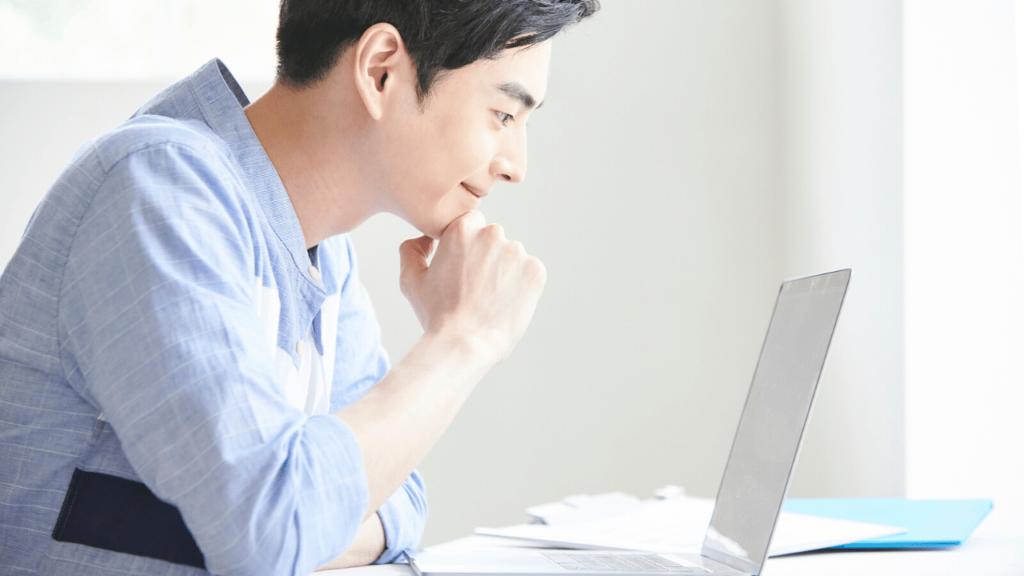 パソコンを覗く若い男性